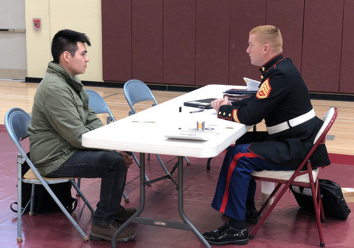 A student talking to someone from the military.