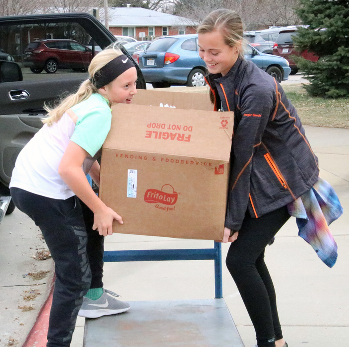 Student Council members carry food to the vehicles for the donation to the Platte County Food Pantry.